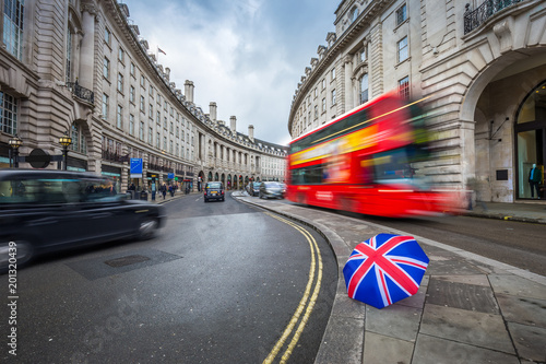 London, England - Iconic red double-decker bus and black taxies on the move on R Canvas Print