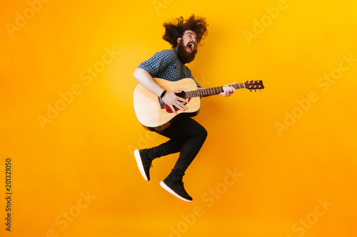 Crazy Bearded Man With Guitar Jumping Over Yellow Background - 201321050