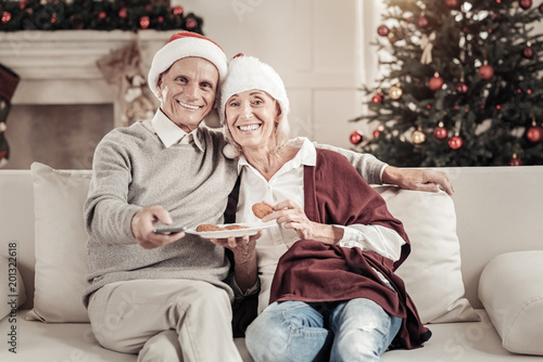 Fototapety, obrazy: Keep smiling. Joyful mature woman feeling happiness while leaning on her husband and holding plate with biscuits
