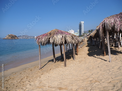 Fotografija  Exotic bamboo huts on sandy beach at bay of ACAPULCO city in Mexico with skycrap