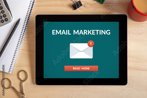 Email marketing concept on tablet screen with office objects on wooden desk. All screen content is designed by me. Top view