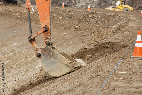 Fotografiet Construction site: Backhoe making banked slope