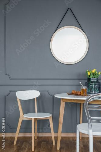 Round mirror above dining set Poster