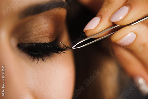 Fototapeta Close up of professional stylist lengthening lashes for female client in a beauty salon