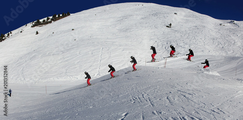 Fotografía Young, female skier, jumping in the air on skis, on a sunny day in Meribel, the French Alps