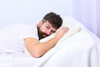 Man in shirt laying on bed, white wall on background. Nap and siesta concept. Macho with beard and mustache sleeping, relaxing, having nap, rest. Guy on tired face sleeping on white sheets and pillow.