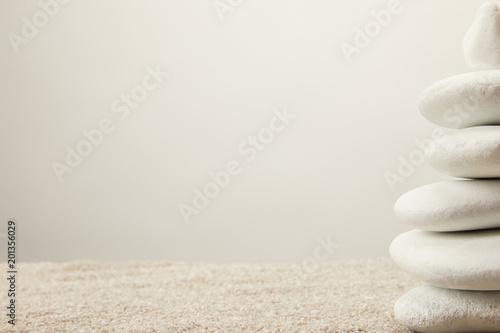 Foto op Plexiglas Stenen in het Zand close up view of arranged white sea stones on sand on grey background