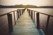 Long wooden bridge in beautiful tropical island beach.