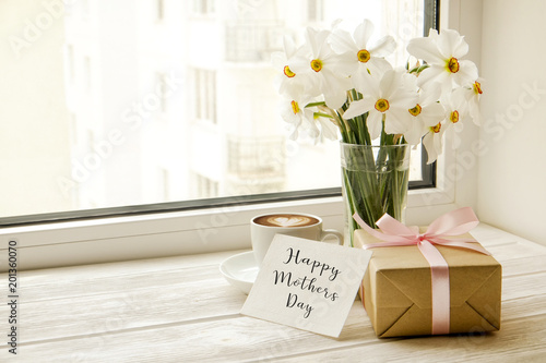 Stickers pour porte Narcisse White yellow daffodil, narcissus flowers in glass vase on wooden windowsill, no window wiev. Happy mother's day text greeting card and craft paper prsent. Close up, copy space, still life, background.