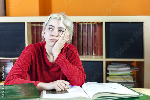 Fotografía  Beautiful bored and tired somnolent student yawning in the morning in a desk at
