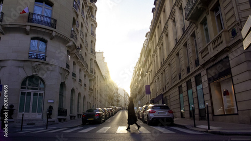 Pedestrian crossing street in European city, woman walking home from work