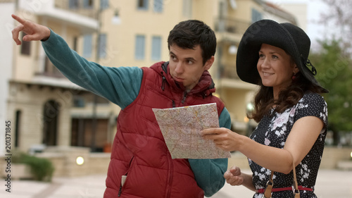 Fotografie, Obraz  Local male citizen showing direction to beautiful female tourist, travel abroad