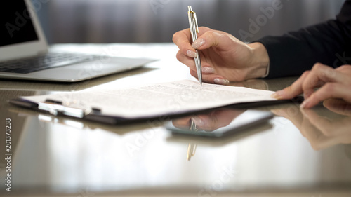 Fotografía  Woman in suit reading terms and conditions of agreement, signing contract
