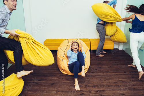 Photo Cheerful young men and women fighting pillows or beanbags in room, one woman sit