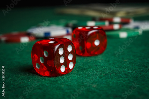 Dice on the poker table against the background of poker chips плакат