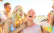 Leinwandbild Motiv Happy friends group having fun at beach party on holi festival summer vacation - Young people laughing together with genuine carefree mood - Youth and friendship concept with multi colored powder game
