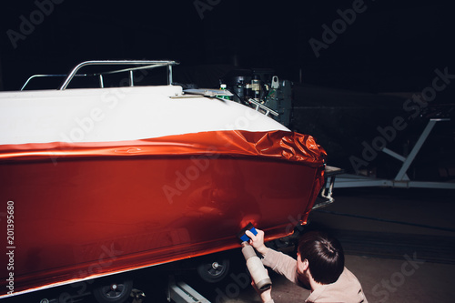 Fotografía  Car wrapping specialist putting vinyl foil or film car wrapping protective film yacht, boat, ship, car, mobile home