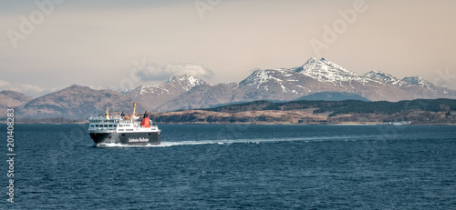 Ferry sailing between Oban and the Isle of Mull with snow capped highland peaks Canvas Print