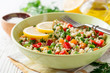 Fresh salad with bulgur and vegetables on white wooden table