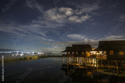 Sky and clouds over illuminated Inle Lake stilt houses at night, Shan State, Myanmar