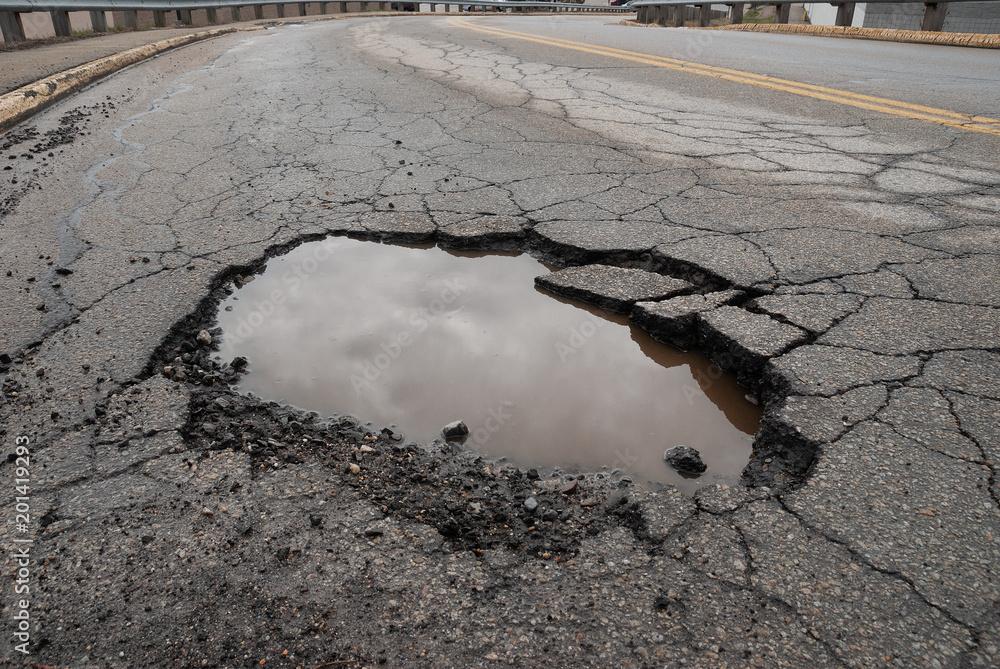 Fototapeta Pothole in road with broken asphalt after spring thaw