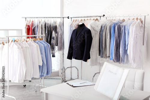 Dry-cleaner's interior with clothes on racks Fototapeta