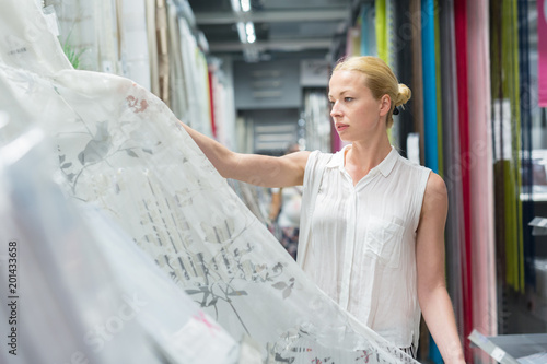 Deurstickers Kamperen Beautiful young caucasian woman buying white curtains for her apartment in modern home decor furnishings store. Shopping in retail store.