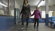 Woman and young girl walking with ice skates on holding hands.