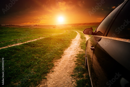 Staande foto Rood paars car on a dirt road in a field of sunflowers and wheat with sunlight