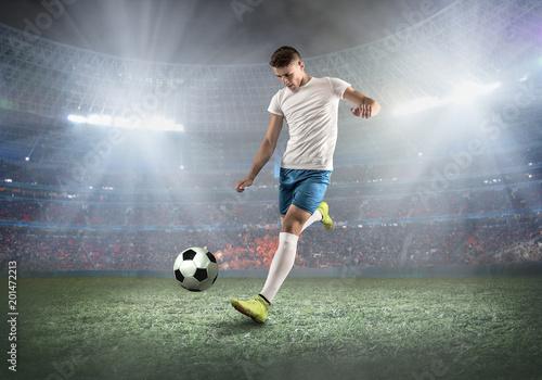 Soccer player on a football field in dynamic action at summer da Fototapeta