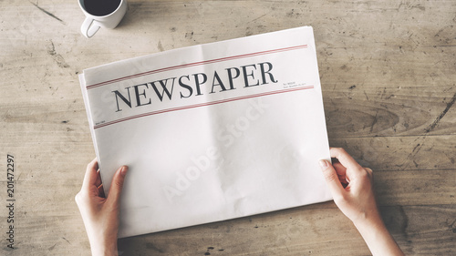 Woman reading newspaper on wooden background