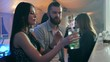 couple make an order and communicates near bar counter against the background of a company of friends in a nightclub