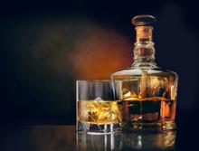 Glass Of Whiskey And Stylish Bottle On Dark Glassy Table