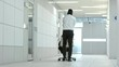 Rear view of african american businessman pushing chair with his belongings on it through hallway of new office center