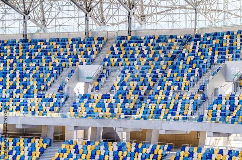 Plakat Siedzi fanów kolorowe plastikowe krzesła na tle stadionu piłkarskiego. Pusta stadium boiska piłkarskiego zielona trawa dla piłki nożnej atletyka areny.
