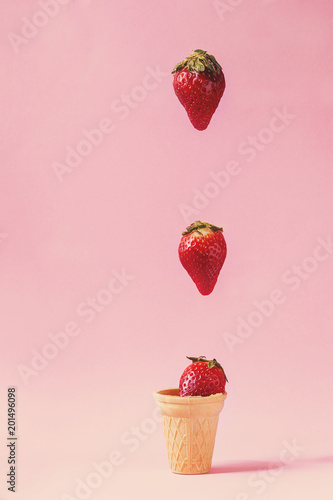 Fresh strawberries falling in waffle cup over pink pastel pin-up background. Copy space.