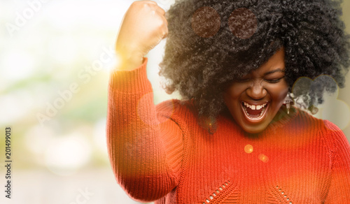 Beautiful african woman happy and excited expressing winning gesture Fototapeta