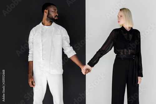 Fotografie, Obraz  multicultural couple holding hands and looking at each other