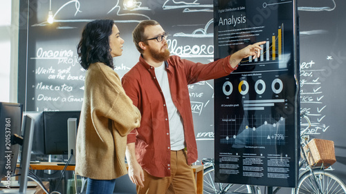 Photo  Female Developer and Male Statistician Use Interactive Whiteboard Presentation Touchscreen to Look at Charts, Graphs and Growth Statistics