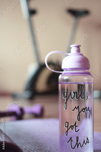 Pink Transparent Water Bottle With Text And Rolled Violet Yoga Mat On Blur Brown Orange Background