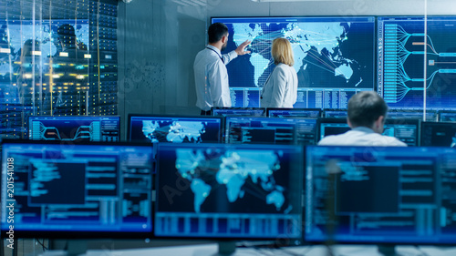 Canvas Print In the System Monitoring Room Two Senior Operators Work on a Big Interactive Map