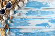 Seashells on blue wooden board with sunglasses. Summer holiday background.