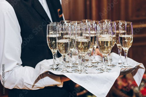 Waiter Serving Stylish Golden Champagne In Glasses On Tray