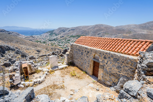 Papiers peints Con. Antique Holy old byzantine greek stone church on the top of the ancient moutnain village pera kastro shining over climber town Pothia at the mediterranean sea, Kalymnos Island, Kos, Dodecanese, Greece
