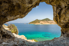 Beautiful Sunny View Through A Rocky Cave To The Greek Blue Sea With Crystal Clear Water From An A Hill With Boats Cruising Fishing Surrounded By Mountains, Patmos Island, Kos, Dodecanese/ Greece