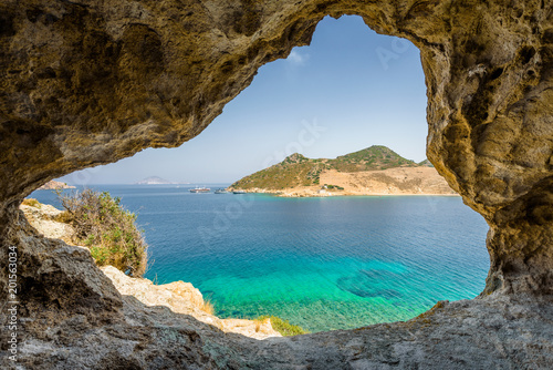 Fotografie, Obraz  Beautiful sunny view through a rocky cave to the greek blue sea with crystal cle