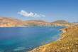 Beautiful sunny coast view to the greek beach Psili Ammos and blue aegean sea with crystal clear water sandy beach with some boats fishing cruising small hills covering, Patmos, Dodecanese, Greece