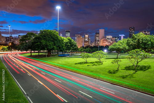 Four Lane Highway Crossing Flamengo Park at Night With Light Trails From Vehicles, and Rio de Janeiro City Downtown in the Horizon