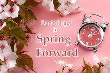 Turn Clocks On Hour Ahead, Star Of Daylight Savings Time Change And Reminder To Spring Forward Concept With Clock On Pink Background With Springtime Flowers And Text - Don't Forget To Spring Forward