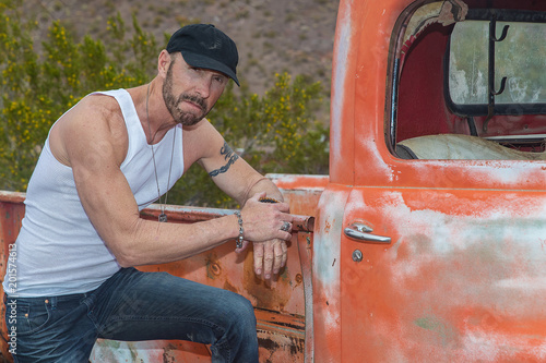 Fotografia, Obraz Mature, strong man with old rusted pickup truck